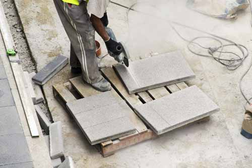 construction worker cutting tiles with electric grinder